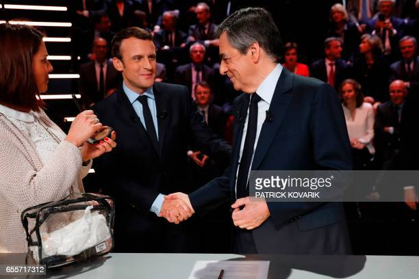 Rightwing Les Republicains party Francois Fillon shakes hands with En Marche movement Emmanuel Macron before a debate organised by the French private...