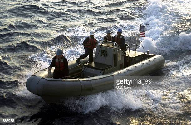 Rigid Hull Inflatable Boat returns to the guided missile cruiser USS Cowpens from the HMAS Darwin February 9 2001 while in the Indian Ocean The two...