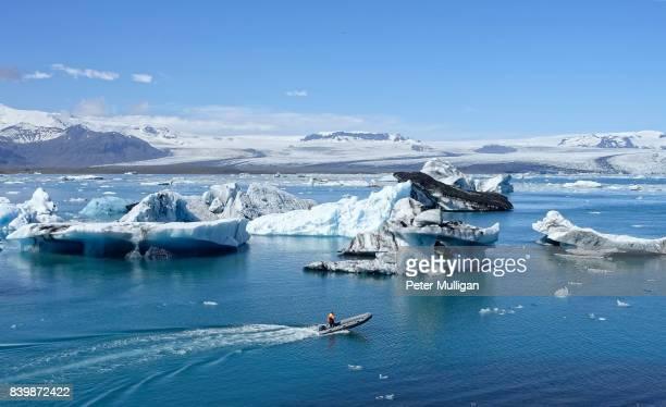 Rigid inflatable boat amongst icebergs in glacier lagoon at Jokulsarlon, Iceland
