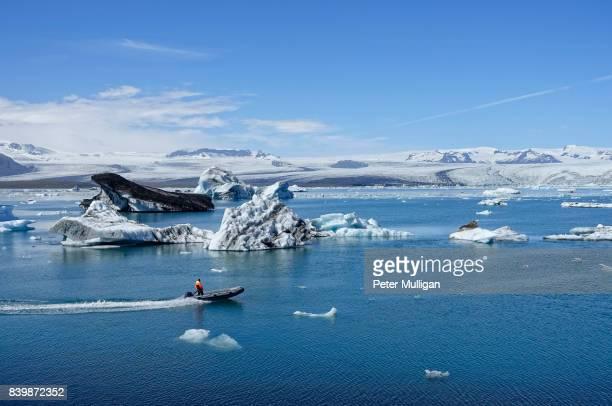 Rigid inflatable boat, icebergs and ice floats, in glacier lagoon at Jokulsarlon, Iceland