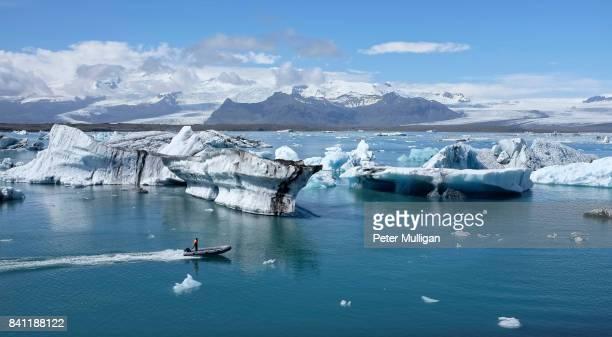 A rigid inflatable boat powers across the glacier lagoon at Jokulsarlon, Iceland