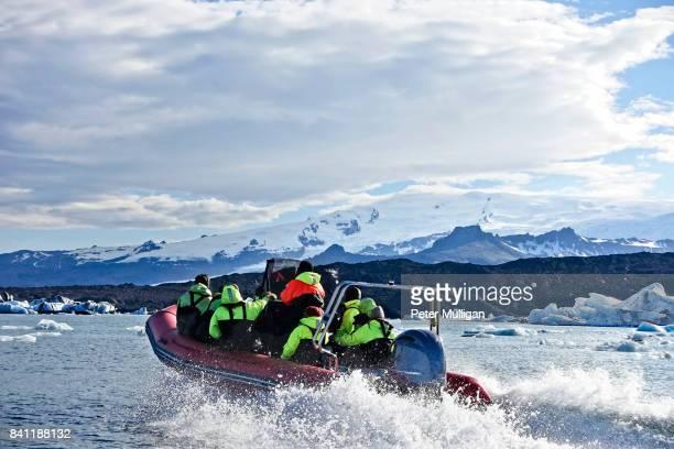 A rigid inflatable boat races across the glacier lake at Jokulsarlon, Iceland