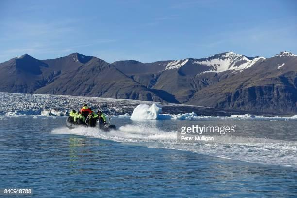 Rigid inflatable boat speeds towards a glacier cliff face at Jökulsárlón, Iceland