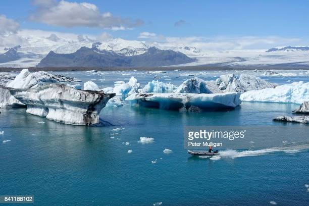 A rigid inflatable boat threads its way through icebergs in the glacier lagoon at Jokulsarlon, Iceland