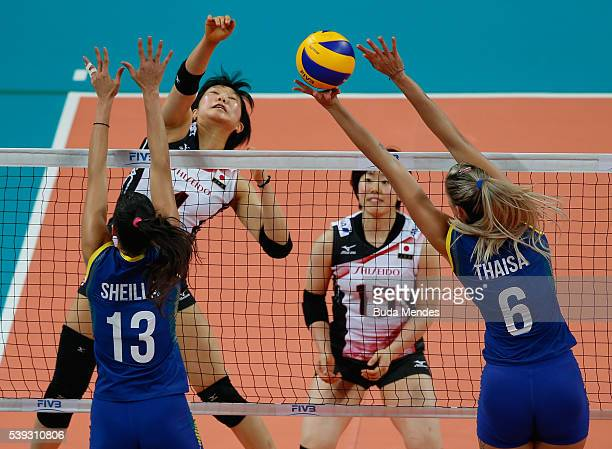 Riho Otake of Japan spikes the ball as Thaisa Menezes and Sheila Castro of Brazil defend during the match between Brazil and Japan on day 2 the FIVB...