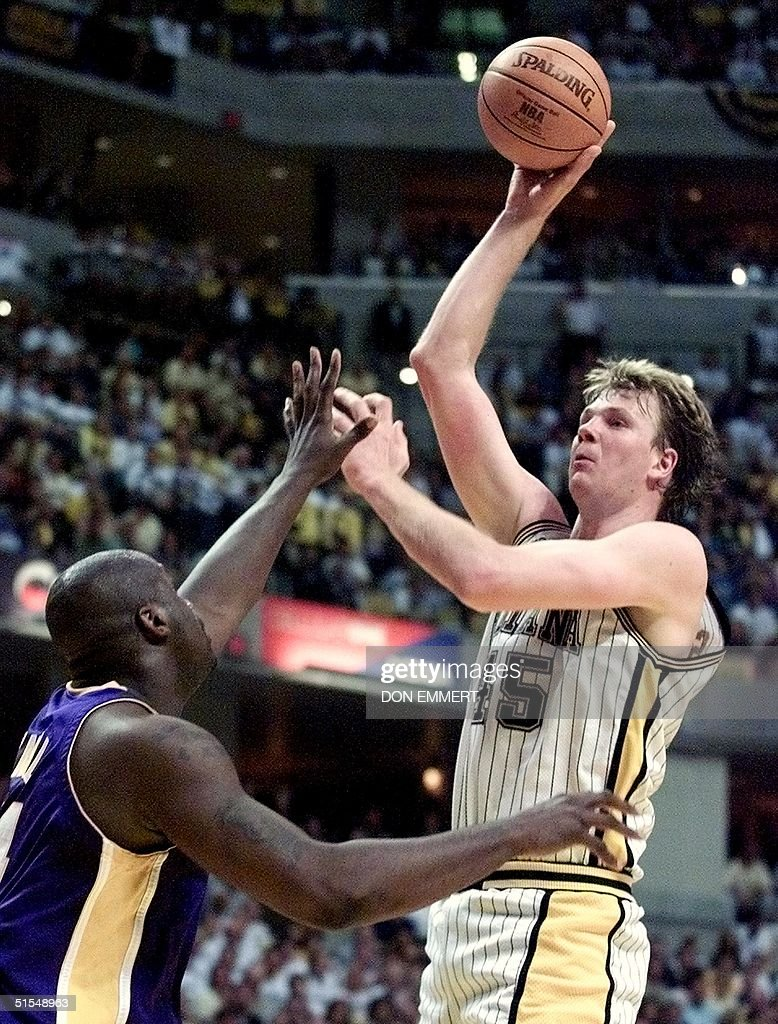 Rik Smits R of the Indiana Pacers shoots over Sh