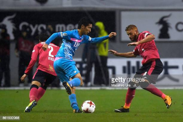Riki Harakawa of Sagan Tosu competes for the ball against Riku Matsuda and Souza of Cerezo Osaka during the JLeague J1 match between Sagan Tosu and...
