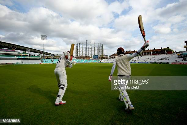 Rikki Clarke and Kumar Sangakkara of Surrey make their way out to open the batting during day three of the Specsavers County Championship Division...