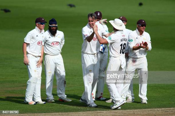 Rikki Clarke of Surrey celebrates with his teammates after dismissing Adam Voges of Middlesex during day one of the Specsavers County Championship...