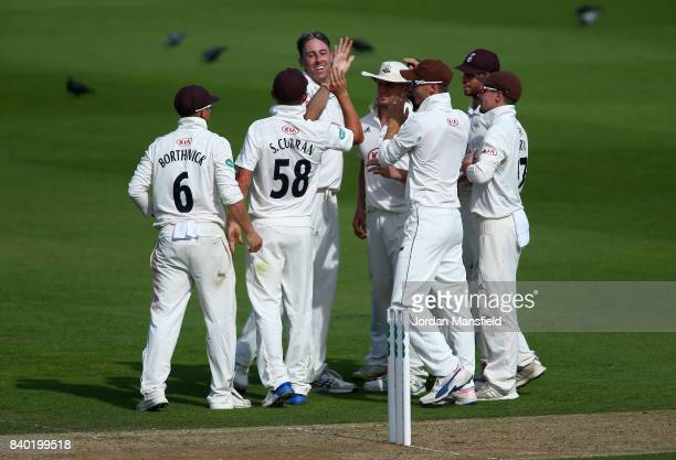 Rikki Clarke of Surrey celebrates with his teammates after dismissing James Franklin of Middlesex during day one of the Specsavers County...