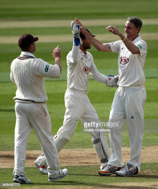 Rikki Clarke of Surrey celebrates with team mates Ben Foakes and Stuart Meaker after taking the wicket of Somerset's Peter Trego during day one of...