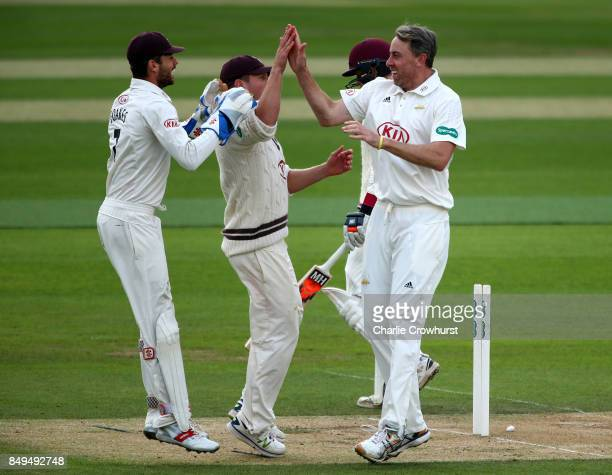 Rikki Clarke of Surrey celebrates with team mates Stuart Meaker and Ben Foakes after taking the wicket of Somerset's Tom Abel during day one of the...