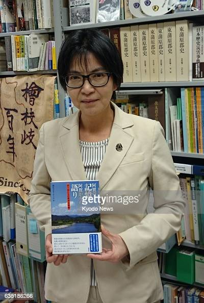 Rikkyo University Professor Reiko Seki holds a book 'Memories of Aga Voices from Aga' compiled by her students to relay stories of Niigata Minamata...