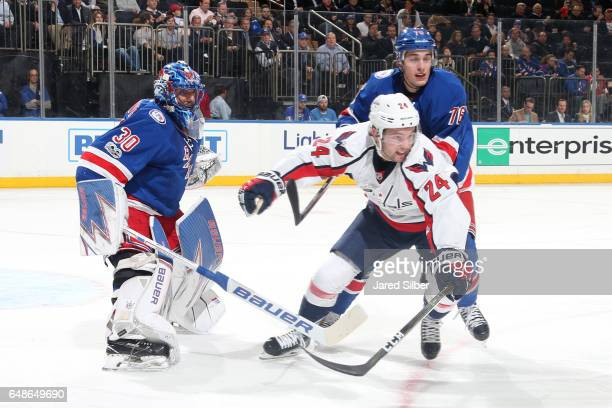 Riley Barber of the Washington Capitals skates against Brady Skjei and Henrik Lundqvist of the New York Rangers at Madison Square Garden on February...