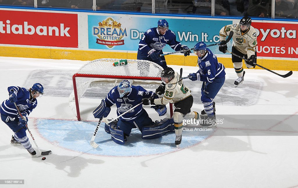 Riley Brace #25 of the Mississauga Steelheads clears a puck for teammate Spencer Martin #30 in an OHL game against the London Knights on December 9, 2012 at the Budweiser Gardens in London, Ontario, Canada. The Knights defeated the Steelheads 5-2 and tied their franchise record of 18 straight wins.