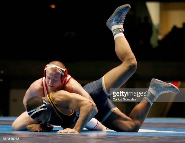 Riley Lefever of Wabash tangles up with Carlos Toribio of Ithaca in the 197 weight class during NCAA Division III Men's Wrestling Championship held...