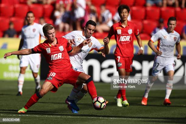 Riley McGree of Adelaide United and Manuel Arana of Brisbane Roar compete during the round 23 ALeague match between Adelaide United and the Brisbane...