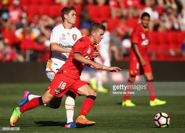 Riley McGree of Adelaide United compets for the ball with Thomas Kristensen of Brisbane Roar during the round 23 ALeague match between Adelaide...