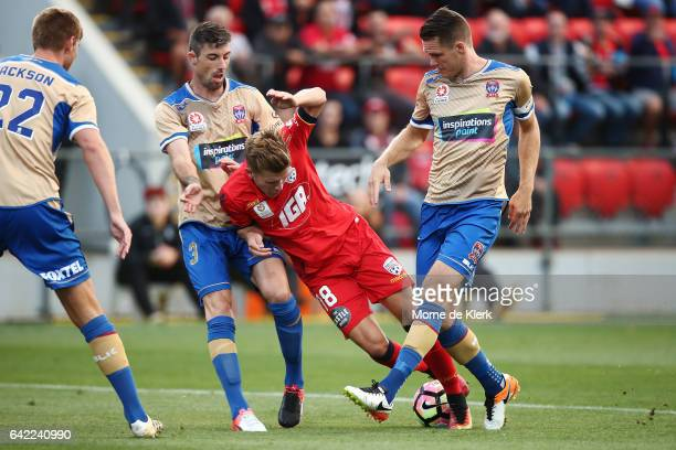 Riley McGree of Adelaide United gets tackled by Nigel Boogaard of the Jets during the round 20 ALeague match between Adelaide United and the...