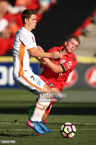 Riley McGree of Adelaide United is tackled by Thomas Kristensen of Brisbane Roar during the round 23 ALeague match between Adelaide United and the...