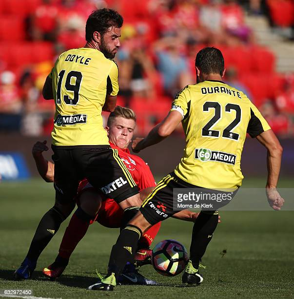 Riley McGree of Adelaide United is tackled by Tom Doyle and Andrew Durante of Wellington Phoenix during the round 17 ALeague match between Adelaide...