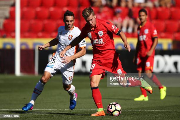 Riley McGree of Adelaide United passes the ball in front of Manuel Arana of Brisbane Roar during the round 23 ALeague match between Adelaide United...