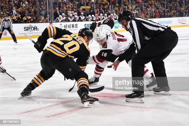 Riley Nash of the Boston Bruins faces off against Max Domi of the Arizona Coyotes at the TD Garden on December 7 2017 in Boston Massachusetts