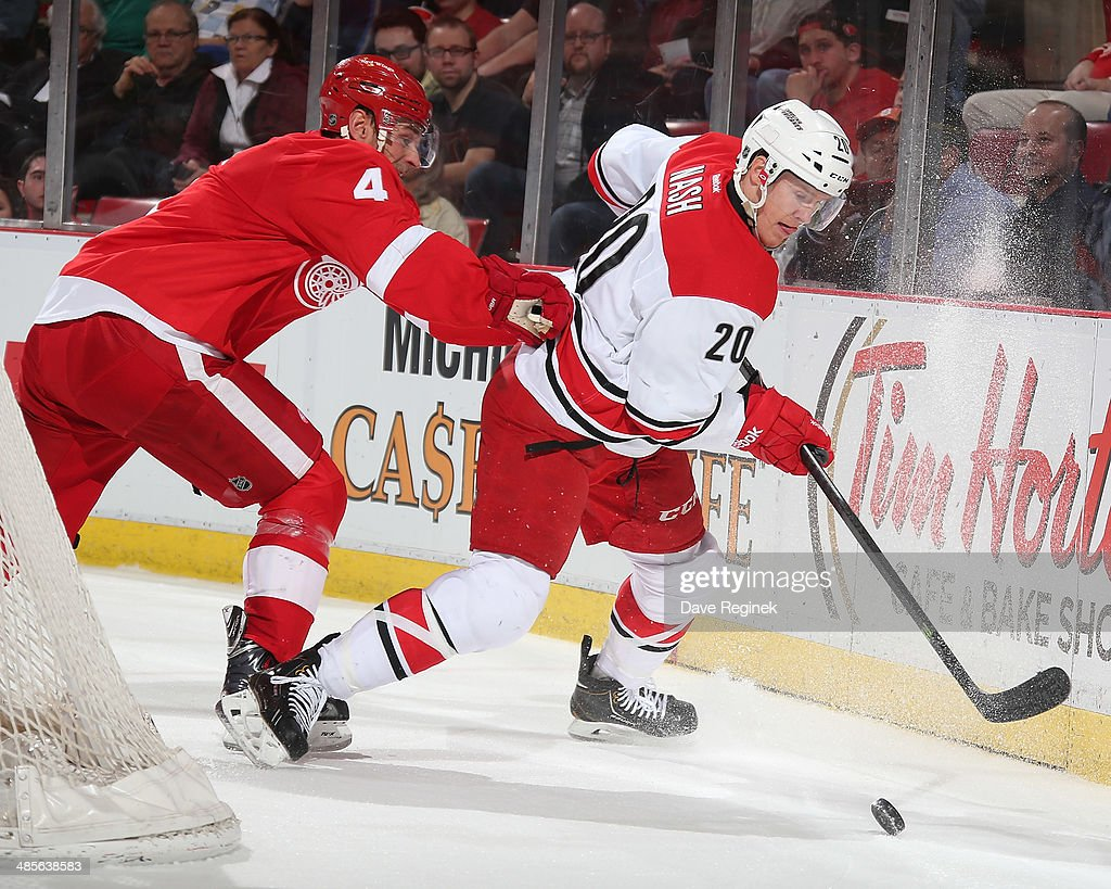 Riley Nash of the Carolina Hurricanes protects the puck in front of Jakub Kindl of the Detroit Red Wings during an NHL game on April 11 2014 at Joe...