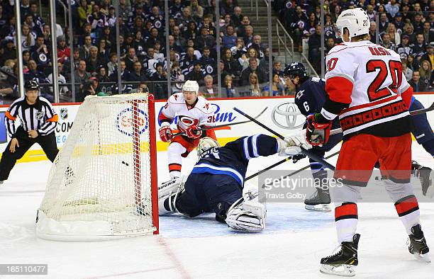 Riley Nash of the Carolina Hurricanes watches as teammate Jussi Jokinen shoots the puck into the net past goaltender Ondrej Pavelec of the Winnipeg...