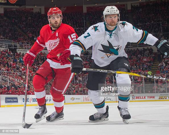 Riley Sheahan of the Detroit Red Wings and Paul Martin of the San Jose Sharks follows the play during an NHL game at Joe Louis Arena on October 22...