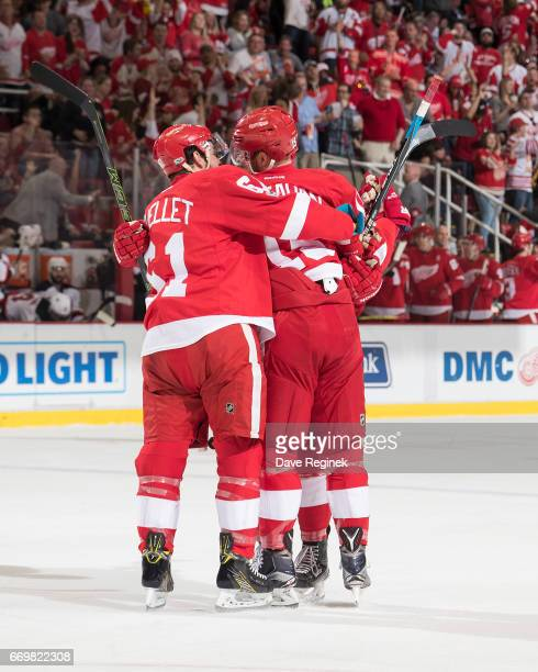 Riley Sheahan of the Detroit Red Wings celebrates his first period first goal of the season with teammates Xavier Ouellet and Robbie Russo during the...