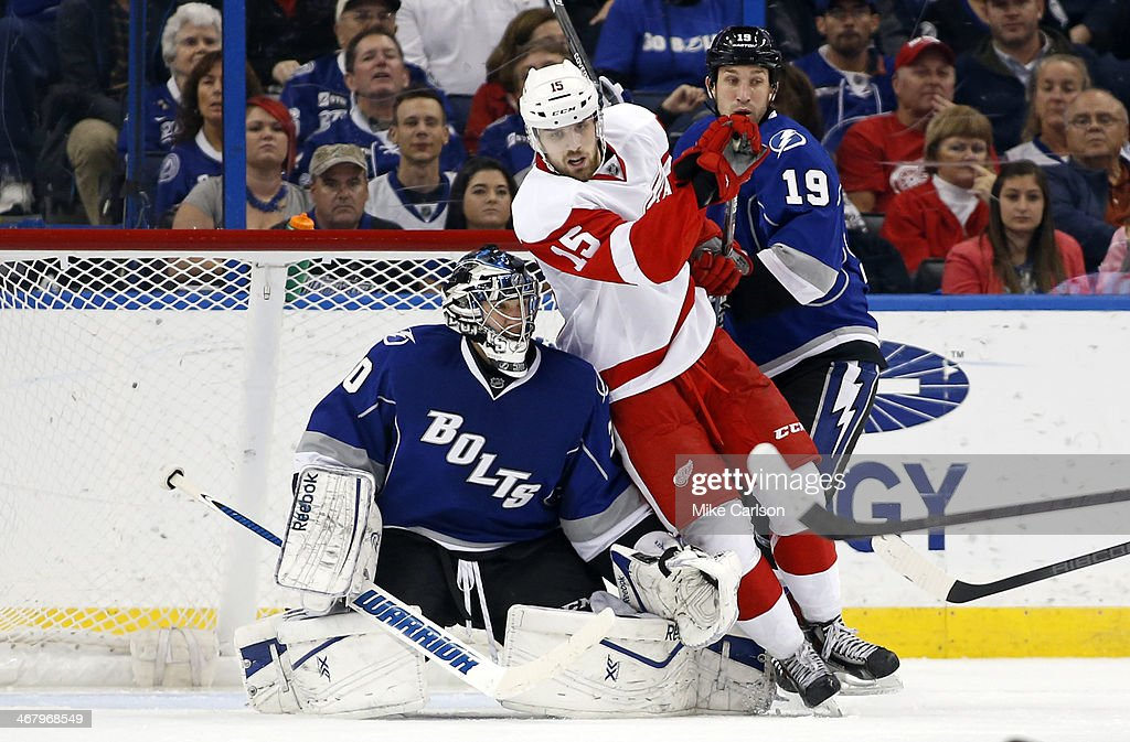 <a gi-track='captionPersonalityLinkClicked' href=/galleries/search?phrase=Riley+Sheahan&family=editorial&specificpeople=7029365 ng-click='$event.stopPropagation()'>Riley Sheahan</a> #15 of the Detroit Red Wings crashes into goalie <a gi-track='captionPersonalityLinkClicked' href=/galleries/search?phrase=Ben+Bishop&family=editorial&specificpeople=700137 ng-click='$event.stopPropagation()'>Ben Bishop</a> #30 of the Tampa Bay Lightning as <a gi-track='captionPersonalityLinkClicked' href=/galleries/search?phrase=B.J.+Crombeen&family=editorial&specificpeople=4505846 ng-click='$event.stopPropagation()'>B.J. Crombeen</a> #19 of the Lightning looks on at the Tampa Bay Times Forum on February 8, 2014 in Tampa, Florida.