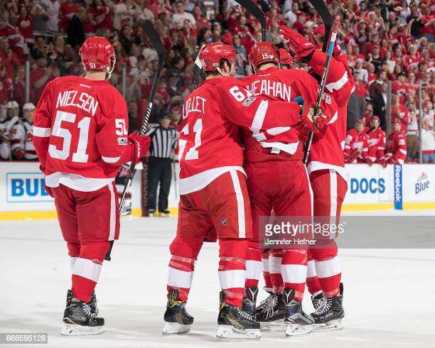 Riley Sheahan of the Detroit Red Wings is congratulated by teammates Xavier Ouellet Darren Helm Robbie Russo and Frans Nielsen following his first...