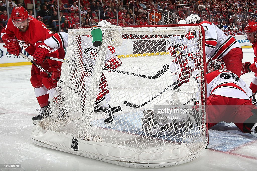<a gi-track='captionPersonalityLinkClicked' href=/galleries/search?phrase=Riley+Sheahan&family=editorial&specificpeople=7029365 ng-click='$event.stopPropagation()'>Riley Sheahan</a> #15 of the Detroit Red Wings shoots the rebound past <a gi-track='captionPersonalityLinkClicked' href=/galleries/search?phrase=Cam+Ward&family=editorial&specificpeople=453216 ng-click='$event.stopPropagation()'>Cam Ward</a> #30 of the Carolina Hurricanes to score a power-play goal during an NHL game on April 11, 2014 at Joe Louis Arena in Detroit, Michigan.