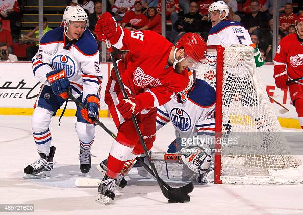 Riley Sheahan of the Detroit Red Wings tries to get a shot off in front of Martin Marincin and goalie Ben Scrivens of the Edmonton Oilers during the...