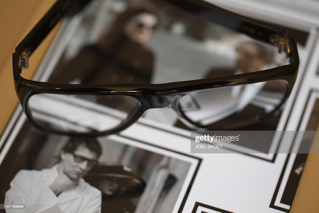 A rim glasses design Yves Saint-Laurent made by the Masion Bonnet are pictured in front of the group's web page at the group's store in Paris on December 6, 2012.