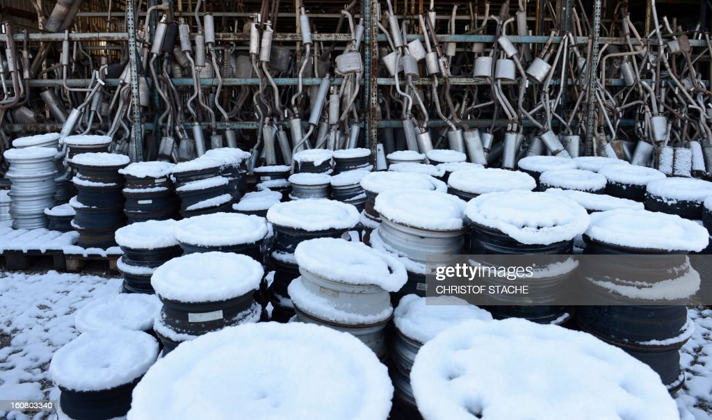 Rims and exhaust silencers of used cars, coverd with snow are pictured in a hall at a recycling company near Munich, southern Germany, on February 6, 2013.