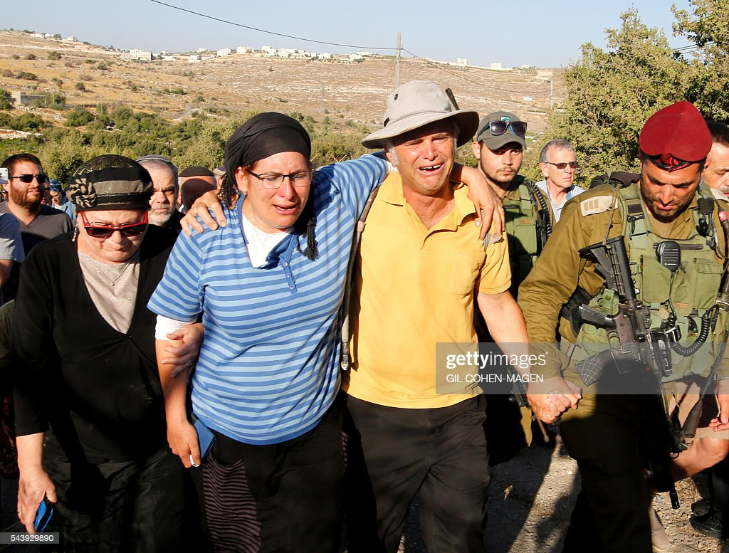 Rina (2-L) and Amihay Yaffe Ariel (2-R) the parents of Israeli Hallel, a 13-year-old girl who was fatally stabbed by a Palestinian attacker in her home, mourn during her funeral in the Kiryat Arba settlement outside the Israeli occupied West Bank city of Hebron on June 30, 2016. The Israeli army said that a young Palestinian killed Hallel in her bed after breaking into her home in the Kiryat Arba settlement outside the flashpoint city of Hebron. Security personnel rushed to the house and fired on the attacker, who wounded a guard before being shot dead, the army said. The girl was taken to hospital in Jerusalem in critical condition and died of her wounds. / AFP / GIL