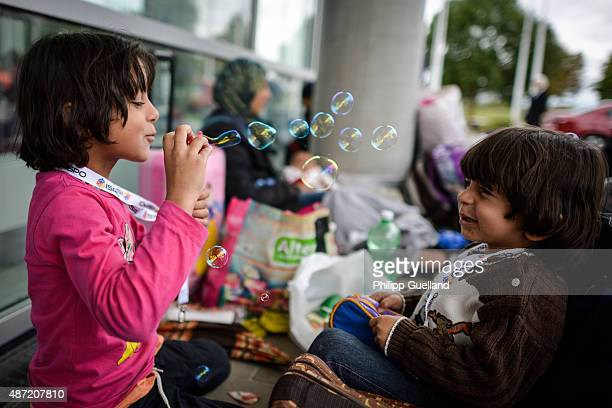 Rinad and Tolen from Syria play with soap bubbles at a refugee accomodation facility in an exhibition hall on September 7 2015 in Munich Germany...