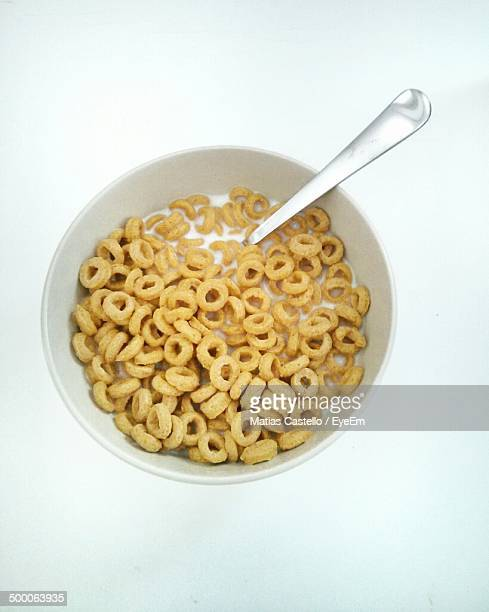 Ring cereal in bowl with milk and spoon over white background