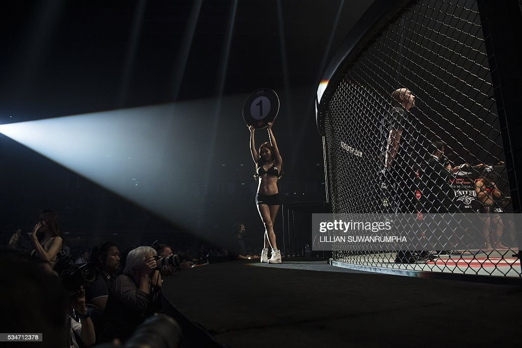 A ring girl parades with a round number during the first ever ONE FC event in Bangkok on May 27, 2016. / AFP / LILLIAN