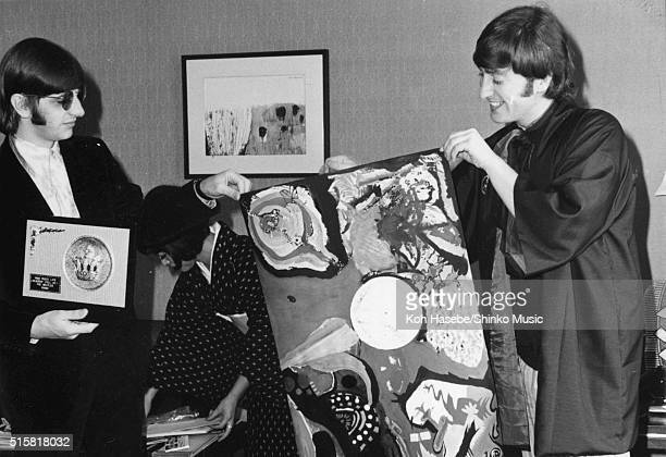 Ringo Starr and John Lennon of the Beatles with Japanese music journalist Rumi Hoshika holding up 'Image of A Woman' painted by The Beatles at Tokyo...