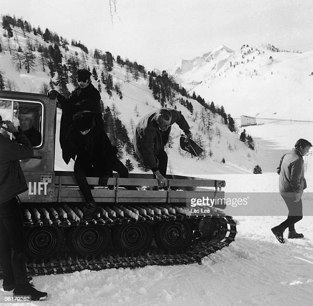 Ringo Starr and John Lennon on a vehicle with caterpillar tracks in the snowy Austrian Alps during the making of the second Beatles film 'Help' 17th...