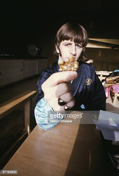 Ringo Starr seems confused by a small carving whilst visiting Tokyo during the Beatles' Asian tour 1966