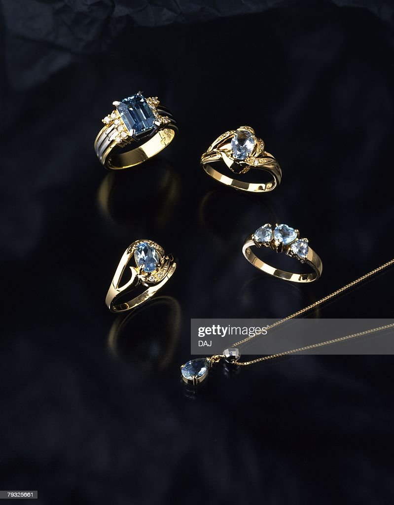Rings and necklace with jewels, high angle view, black background : Stock Photo