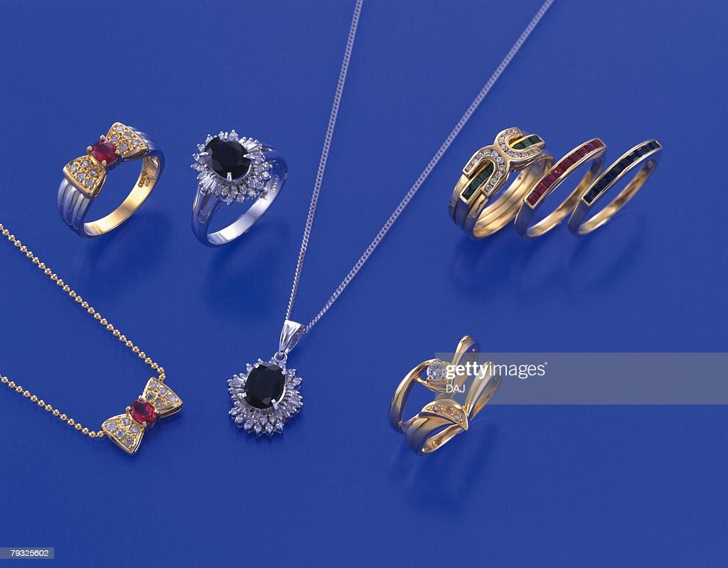 Rings and necklace with jewels, high angle view, colored background : Stock Photo