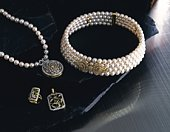 Rings and necklaces with pearls on marble surface, high angle view