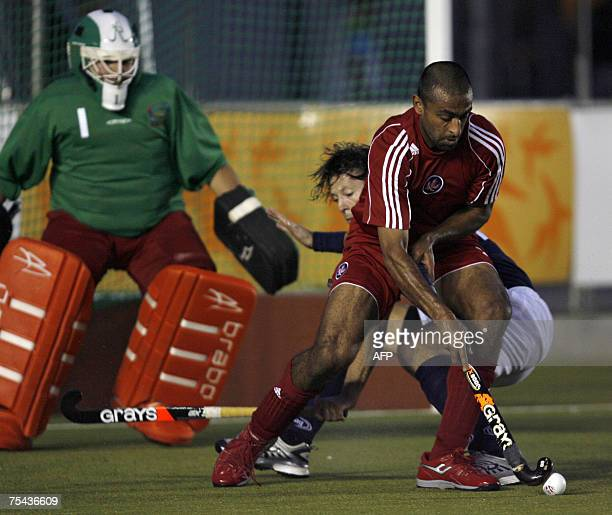 Ravi Kahlon of Canada dribbles the ball against the mark of Janiek Braaksma and goalkeeper Daan Vismans of the Netherlands Antilles during their XV...