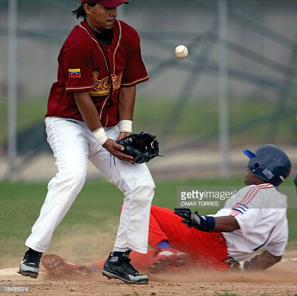 Venezuelan third base Jose Nieves losses the ball in front of Cuban center fielder Giorvis Duvergel's slide during the baseball game at the Cidade do...