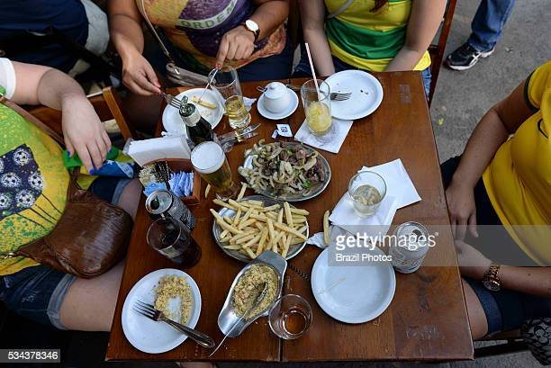 Rio de Janeiro lifestyle people enjoy leisure time at sidewalk table in a typical Rio bar having chope and appetizers fillet with onion French fries...